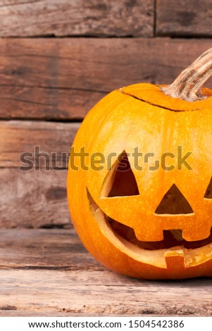 Pumpkin carved as Jack-O-Lantern. Cropped image of funny Halloween pumpkin on wooden background. Halloween pumpkin carving ideas.