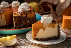 Pumpkin cheesecake. Curd cake with caramel, nuts, whipped cream, pumpkin, apples and autumn leaves on the background.