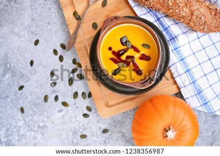 Pumpkin cream soup in a small bowl and on a wooden board on a kitchen surface with a whole pumpkin and sliced bread beside it - autumnal feasting #1238356987
