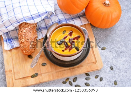 Pumpkin cream soup in a small bowl and on a wooden board on a kitchen surface with a whole pumpkin and sliced bread beside it - autumnal feasting #1238356993