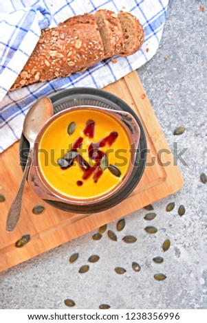 Pumpkin cream soup in a small bowl and on a wooden board on a kitchen surface with a whole pumpkin and sliced bread beside it - autumnal feasting #1238356996
