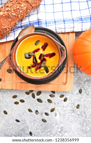 Pumpkin cream soup in a small bowl and on a wooden board on a kitchen surface with a whole pumpkin and sliced bread beside it - autumnal feasting #1238356999