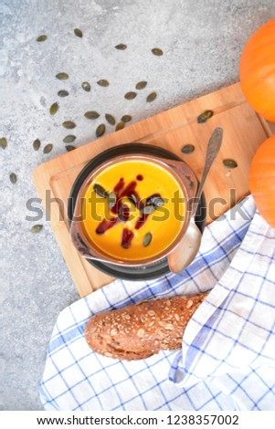 Pumpkin cream soup in a small bowl and on a wooden board on a kitchen surface with a whole pumpkin and sliced bread beside it - autumnal feasting #1238357002