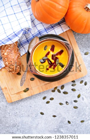 Pumpkin cream soup in a small bowl and on a wooden board on a kitchen surface with a whole pumpkin and sliced bread beside it - autumnal feasting #1238357011
