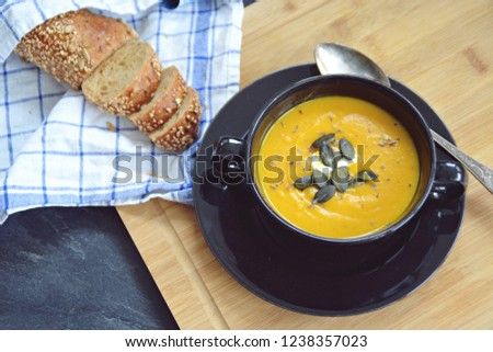 Pumpkin cream soup in a small bowl and on a wooden board on a kitchen surface with a whole pumpkin and sliced ​​bread beside it - autumnal feasting #1238357023
