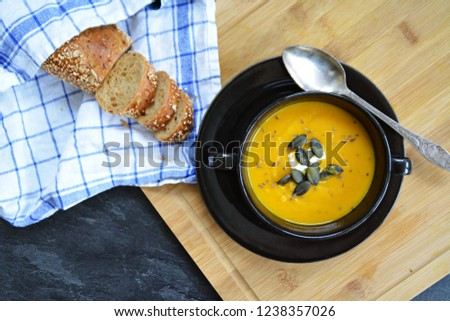 Pumpkin cream soup in a small bowl and on a wooden board on a kitchen surface with a whole pumpkin and sliced ​​bread beside it - autumnal feasting #1238357026