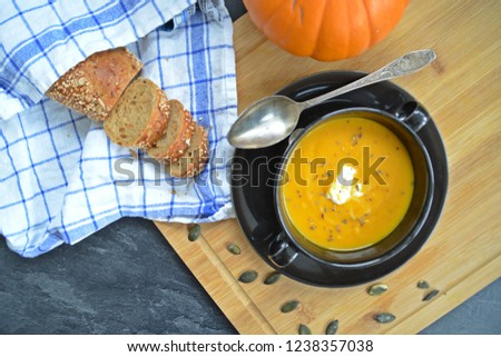 Pumpkin cream soup in a small bowl and on a wooden board on a kitchen surface with a whole pumpkin and sliced ​​bread beside it - autumnal feasting #1238357038