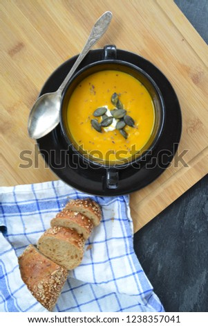 Pumpkin cream soup in a small bowl and on a wooden board on a kitchen surface with a whole pumpkin and sliced ​​bread beside it - autumnal feasting #1238357041