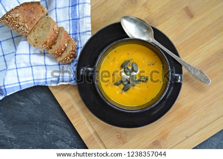 Pumpkin cream soup in a small bowl and on a wooden board on a kitchen surface with a whole pumpkin and sliced ​​bread beside it - autumnal feasting #1238357044