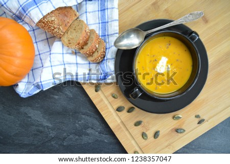 Pumpkin cream soup in a small bowl and on a wooden board on a kitchen surface with a whole pumpkin and sliced ​​bread beside it - autumnal feasting #1238357047