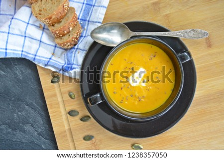 Pumpkin cream soup in a small bowl and on a wooden board on a kitchen surface with a whole pumpkin and sliced ​​bread beside it - autumnal feasting #1238357050