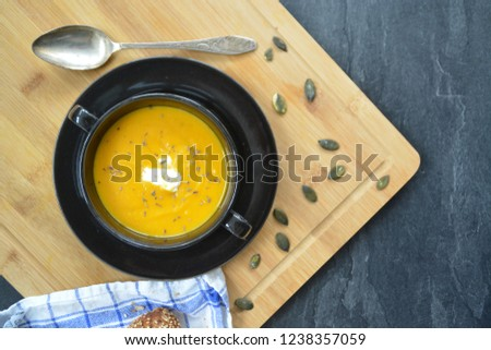 Pumpkin cream soup in a small bowl and on a wooden board on a kitchen surface with a whole pumpkin and sliced ​​bread beside it - autumnal feasting #1238357059