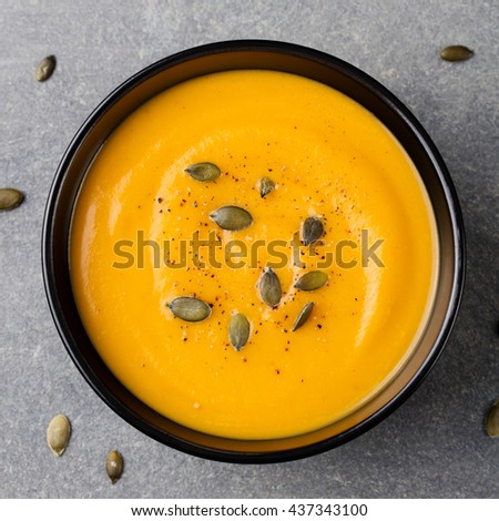 Pumpkin cream soup with pumpkin seeds in a black bowl. Grey stone background. Top view