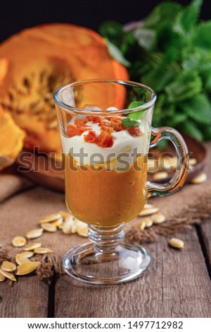 Pumpkin dessert with yogurt and dried apricots.Homemade autumn dessert of pumpkin mousse in glass glasses on a wooden rustic table.Pumpkin keto mousse with low carbs on a dark background. The concept  #1497712982