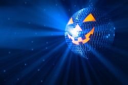 pumpkin disco ball at Halloween party, jack o'lantern with shiny blue rays in smoke