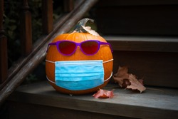 Pumpkin dressed up for Halloweeen with COVID PPE face mask