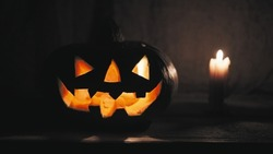 Pumpkin for Halloween with a scary face on a wooden porch. Concept of feast of night of all Saints. Candles are burning inside the pumpkin