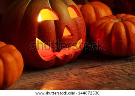 Pumpkin head and small pumpkins in dark with copy space.