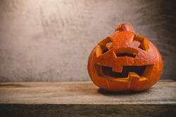 Pumpkin head on a wooden table on a background of a gray wall with autumn leaves