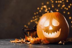 Pumpkin jack o'lantern and Halloween decor on table against blurred background, space for text