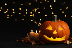 Pumpkin jack o'lantern, candles and autumn leaves  on table against blurred background, space for text. Halloween decor