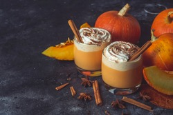 Pumpkin latte drink. Autumn coffee with spicy pumpkin flavor and cream on a dark background. Seasonal Fall Drinks for Halloween and Thanksgiving