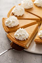 Pumpkin layered cheesecake pie with whipped cream sliced