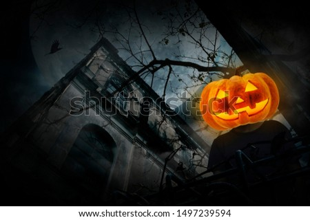 Pumpkin monster head on man body standing over grunge castle, dead tree, bird fly, full moon and cloudy spooky sky, Halloween mystery concept