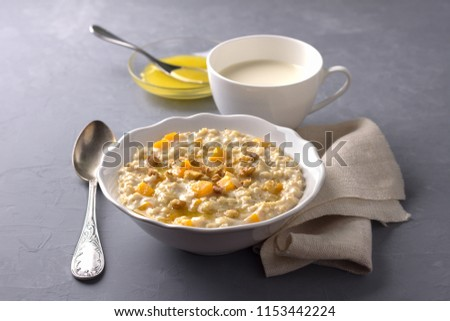 Pumpkin oatmeal with honey and nuts on a gray background. healthy delicious homemade breakfast