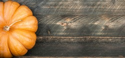 Pumpkin on dark rustic wooden table. Halloween background with pumpkin. Autumn, halloween, thanksgiving, holidays, autumn sale concept. Copy space long format for banner. Top view