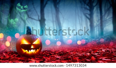 Pumpkin On Red Leaves In Spooky Forest With Ghost Smoke - Halloween