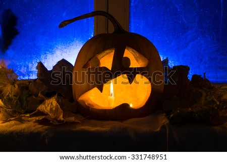 Pumpkin photo for a holiday Halloween. The scared pumpkin against an old window, candles and leaves with blue illumination
