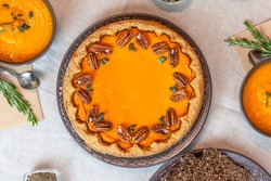 Pumpkin pie decorated with pecans on a served table for an autumn party food