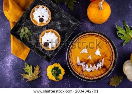 Pumpkin pie in shape of jack-o-lantern and lemon tart. In shape of ghost. Halloween food.