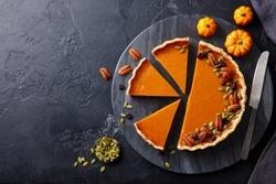 Pumpkin pie on marble cutting board. Dark background. Copy space. Top view.