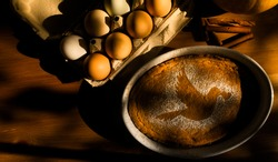 Pumpkin pie sprinkled with sugar and cinnamon forming a picture of a dove carrying a heart in its beak on on a wooden table. Love pie.