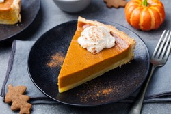 Pumpkin pie, tart made for Thanksgiving day with whipped cream on a black plate. Grey stone background