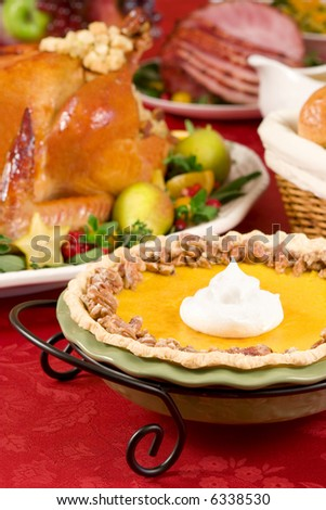 Pumpkin pie topped with pecans and cream