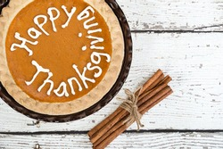 Pumpkin pie with Happy Thanksgiving text. Displayed on vintage wooden table with cinnamon sticks. Top view.