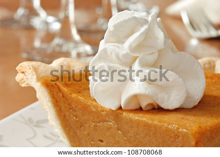 Pumpkin pie with swirls of whipped cream on decorative plate.  Elegant dinnerware in soft focus in background.  Macro with shallow dof.