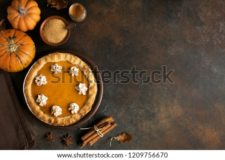 Pumpkin Pie with whipped cream and cinnamon on rustic background, top view. Homemade pastry for Thanksgiving traditional Pumpkin Pie. #1209756670