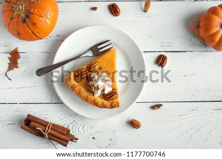 Pumpkin Pie with whipped cream, pecan nut and cinnamon on white wooden background, top view, copy space. Homemade autumn pastry for Thanksgiving - piece of pumpkin pie. #1177700746
