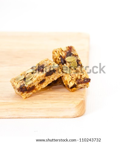 Pumpkin seed and raisin flapjack on a wooden chopping board, white background
