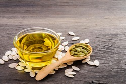Pumpkin seed oil in a cup with pumpkin seeds placed on an old wooden table.