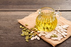 Pumpkin seed oil in a pitcher with pumpkin seeds placed on an old wooden table.