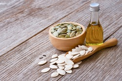 Pumpkin seed oil in glass bottle and dried pumpkinseed in wooden bowl and scoop isolated on wooden table background.