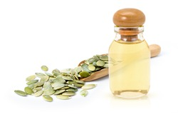 Pumpkin seed oil in glass bottle and dried pumpkinseed in wooden scoop isolated on white  background.
