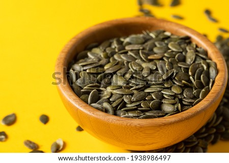 Pumpkin seed or pepita in wooden bowl on yellow background. Modern ingredients background. Copy space .Close up Foto stock ©
