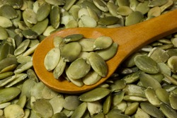 Pumpkin seeds and wooden spoon as background
