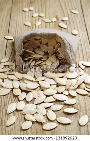 Pumpkin seeds in a sack on the wooden table